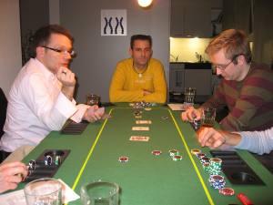 Pokertisch mit Pokerspielern und Karten